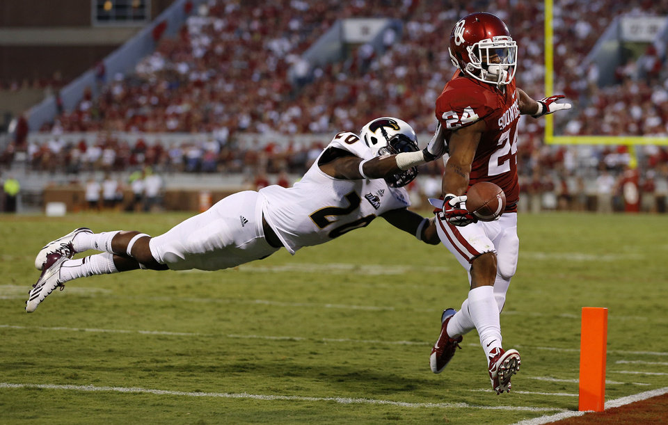 Photo - Oklahoma's Brennan Clay scores a touchdown beside Louisiana Monroe's Justin Backus (20) during a college football game between the University of Oklahoma Sooners (OU) and the University of Louisiana Monroe Warhawks at Gaylord Family-Oklahoma Memorial Stadium in Norman, Okla., on Saturday, Aug. 31, 2013. Oklahoma won 34-0. Photo by Bryan Terry The Oklahoman