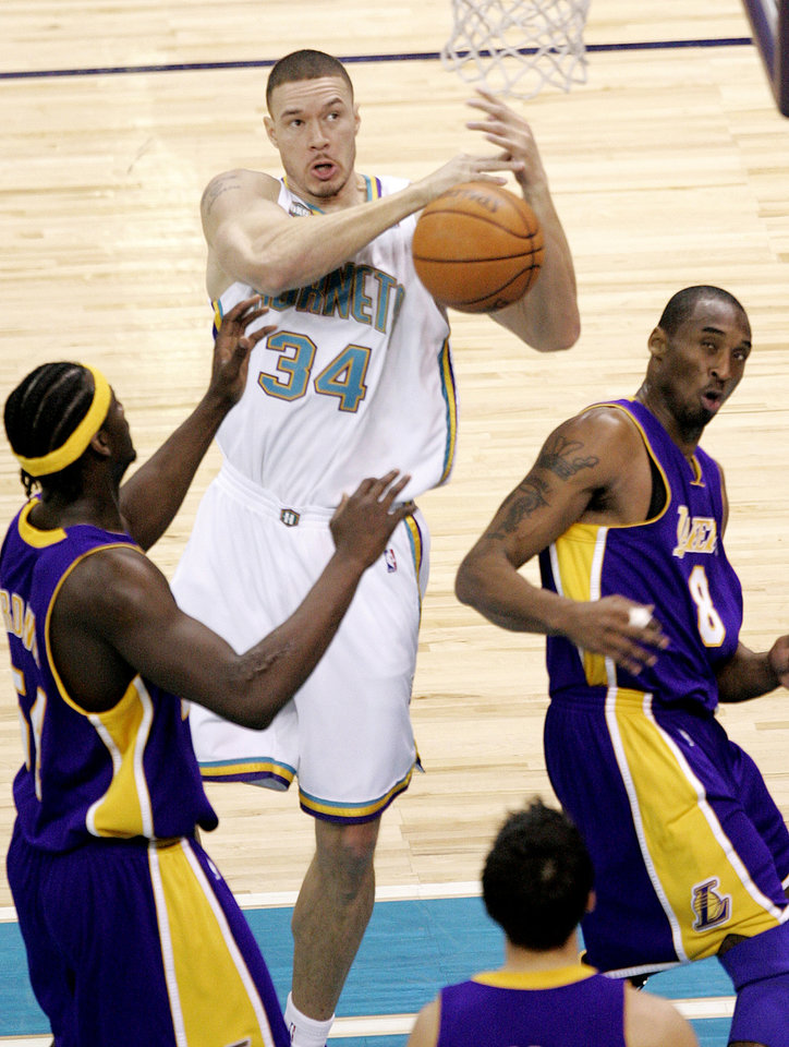 Photo - Aaron Williams of the Hornets grabs a rebound between Kwame Brown and Kobe Bryant of the Los Angeles Lakers during the New Orleans/Oklahoma City Hornets NBA basketball game against the Lakers at the Ford Center in Oklahoma City, Feb. 4, 2006.  By Bryan Terry/The Okahoman