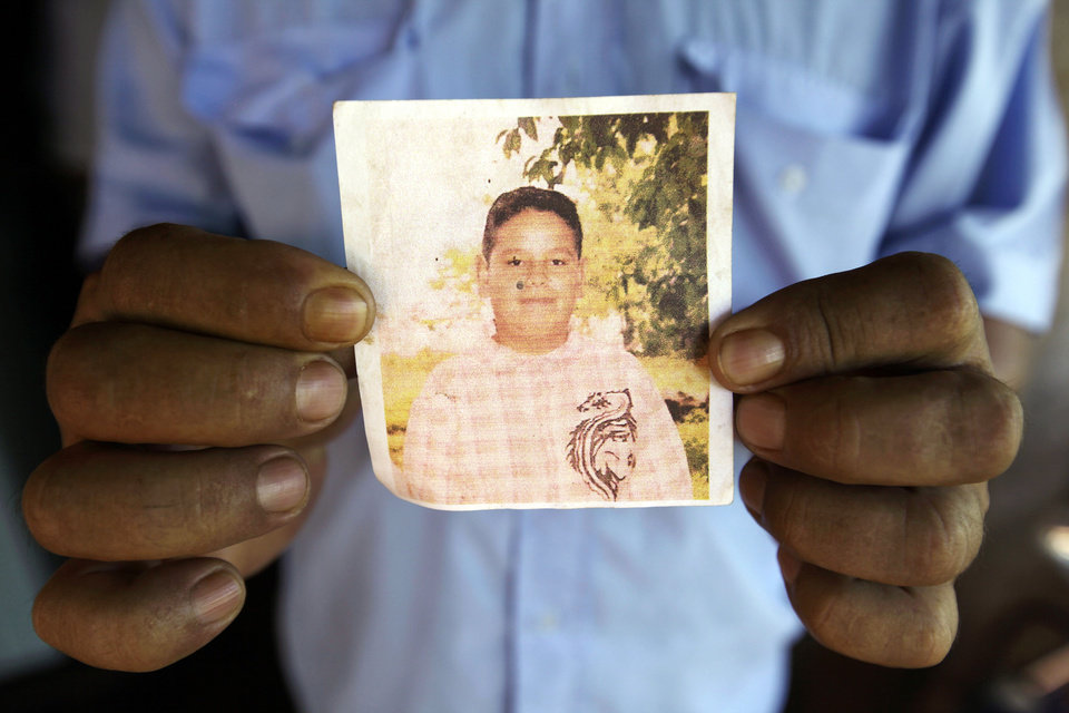 "In this Nov. 13, 2012 photo, Roberto Ortega holds a photocopy of a portrait of his only son Luciano in the Yvy Pyta settlement near Curuguaty, Paraguay.  Luciano, 18, died during the ""Massacre of Curuguaty"" on June 15 when negotiations between farmers occupying a rich politician's land ended with a barrage of bullets that killed 11 farmers and 6 police officers. Ortega had sold his tiny shack and plot of land to a neighbor and marched onto the ranch with his wife, carrying all their remaining possessions. (AP Photo/Jorge Saenz)"