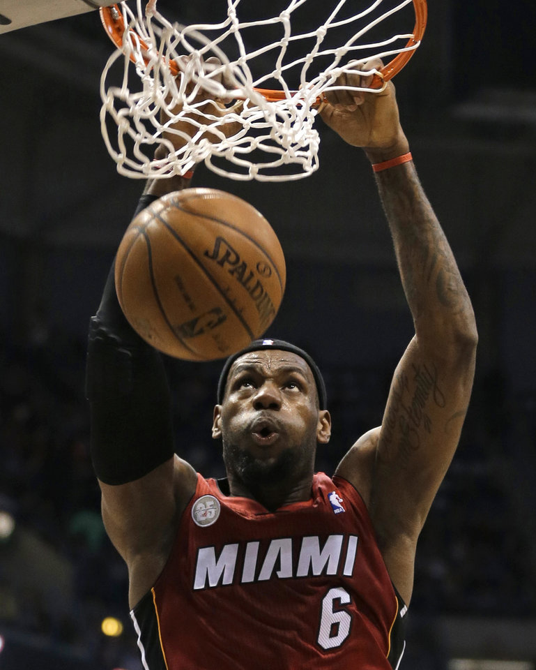 Photo - Miami Heat's LeBron James dunks against the Milwaukee Bucks in the first half of an NBA basketball game Friday, March 15, 2013, in Milwaukee. (AP Photo/Jeffrey Phelps)