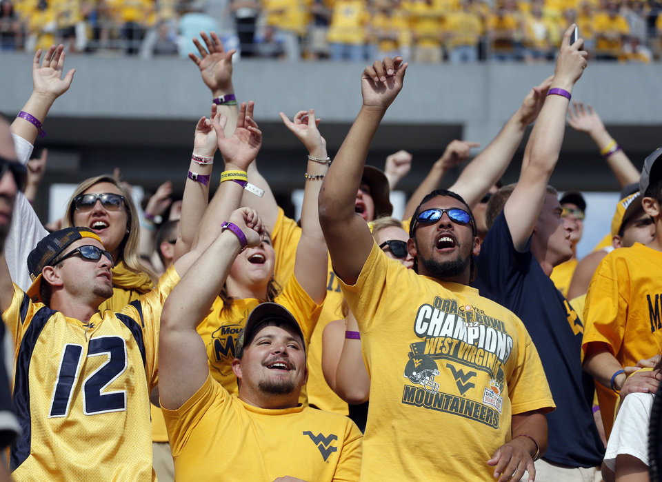 Photo - West Virginia fans celebrate late in the fourth quarter during the second half of a college football game between the Oklahoma State University and West Virginia University on Mountaineer Field at Milan Puskar Stadium in Morgantown, W. Va.,   Saturday, Sept. 28, 2013. Photo by Sarah Phipps, The Oklahoman