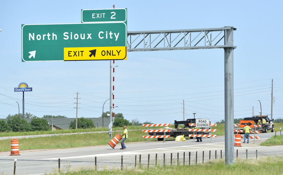 Photo - Workers set up signs and cones to close the northbound lanes of Interstate 29, at North Sioux City, SD, Thursday, June 19, 2014. The interstate was closed at noon to allow a flood control levee to be built across the road. Cities along the river were working to battle record flooding from the Big Sioux River. (AP Photo/Sioux City Journal, Tim Hynds)