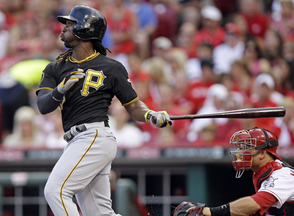 Photo - Pittsburgh Pirates' Andrew McCutchen hits a solo home run off Cincinnati Reds starting pitcher Mat Latos in the fourth inning of a baseball game, Friday, July 11, 2014, in Cincinnati. Devin Mesoraco catches at right. (AP Photo/Al Behrman)