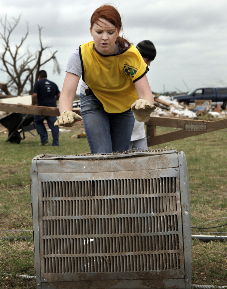 Heather Smith from Dallas with Mormon Helping Helping Hands rolls a air conditioning unit across a yard at a home in Moore on May 27, 2013. Photo by KT King, The Oklahoman