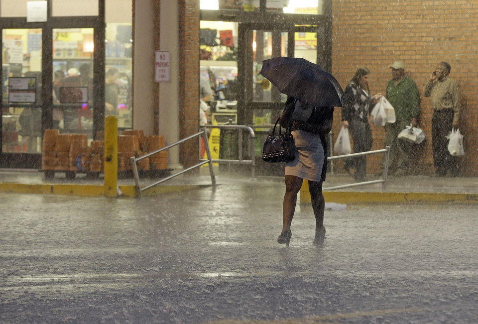 Photo - A woman walks through a heavy rain as others wait for the rain to stop at a grocery store in Montgomery, Ala., Monday, March 18, 2013. A line of severe thunderstorms crossed the state, bringing heavy rain and high winds. (AP Photo/Dave Martin)