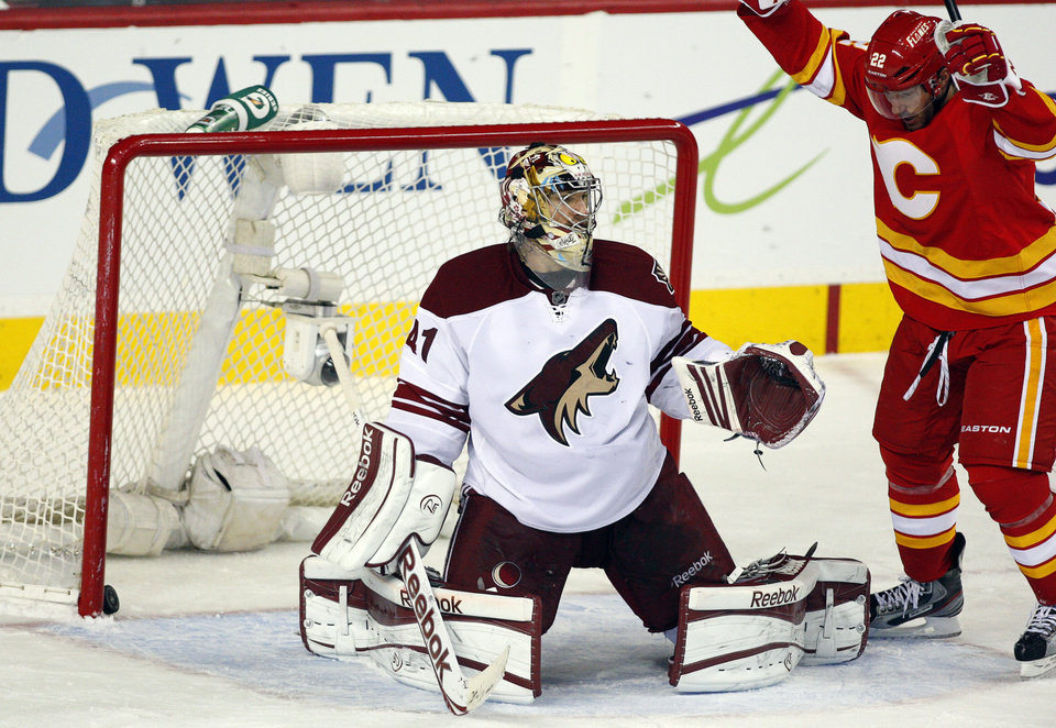Photo - Phoenix Coyotes goalie Mike Smith, left, reacts as Calgary Flames' Lee Stempniak celebrates his team's goal during the second period of an NHL hockey game in Calgary, Alberta, Sunday, Feb. 24, 2013. (AP Photo/The Canadian Press, Jeff McIntosh)