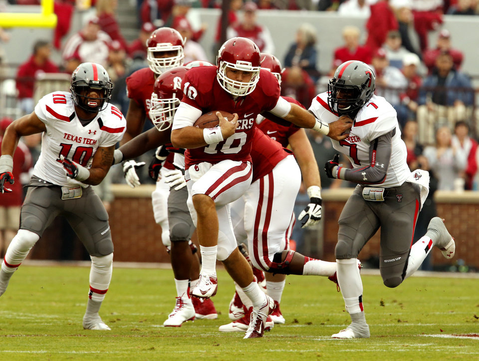 Blake Bell (10) carries early pursued by Texas Tech's Will Smith (7) in the first quarter during a college football game between the University of Oklahoma Sooners (OU) and the Texas Tech Red Raiders at Gaylord Family-Oklahoma Memorial Stadium in Norman, Okla., on Saturday, Oct. 26, 2013. Photo by Steve Sisney, The Oklahoman