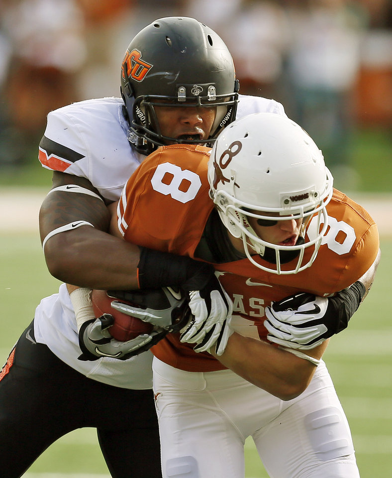 Oklahoma State's Joe Mitchell (29) tackles UT's Jaxon Shipley (8) during a college football game between the Oklahoma State University Cowboys (OSU) and the University of Texas Longhorns (UT) at Darrell K Royal - Texas Memorial Stadium in Austin, Texas, Saturday, Nov. 16, 2013. Photo by Nate Billings, The Oklahoman
