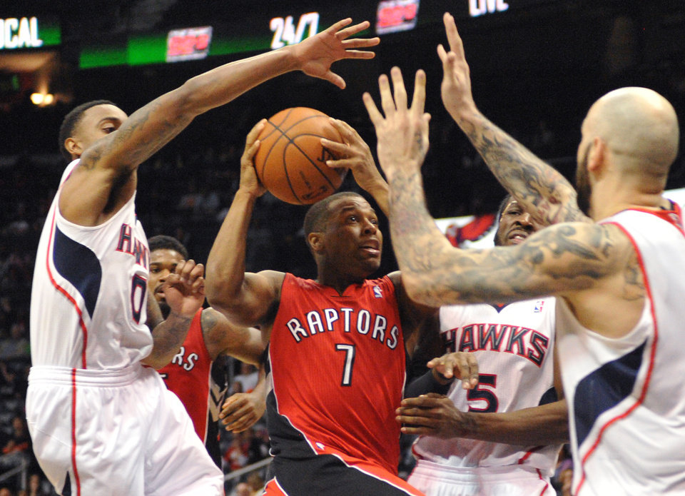 Photo - Toronto Raptors' Kyle Lowry (7) is blocked by Atlanta Hawks' Jeff Teague (0), DeMarre Carroll (5), and Pero Antic (6)  during overtime of their NBA basketball game Tuesday, March 18, 2014, in Atlanta. Atlanta won 118-113. (AP Photo/David Tulis)