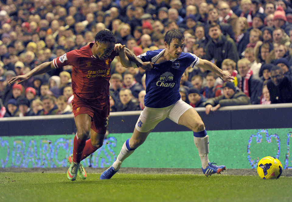 Photo - Liverpool's Raheem Sterling, left, tackles Everton's Leighton Baines during their English Premier League soccer match at Anfield in Liverpool, England, Tuesday Jan. 28, 2014. (AP Photo/Clint Hughes)