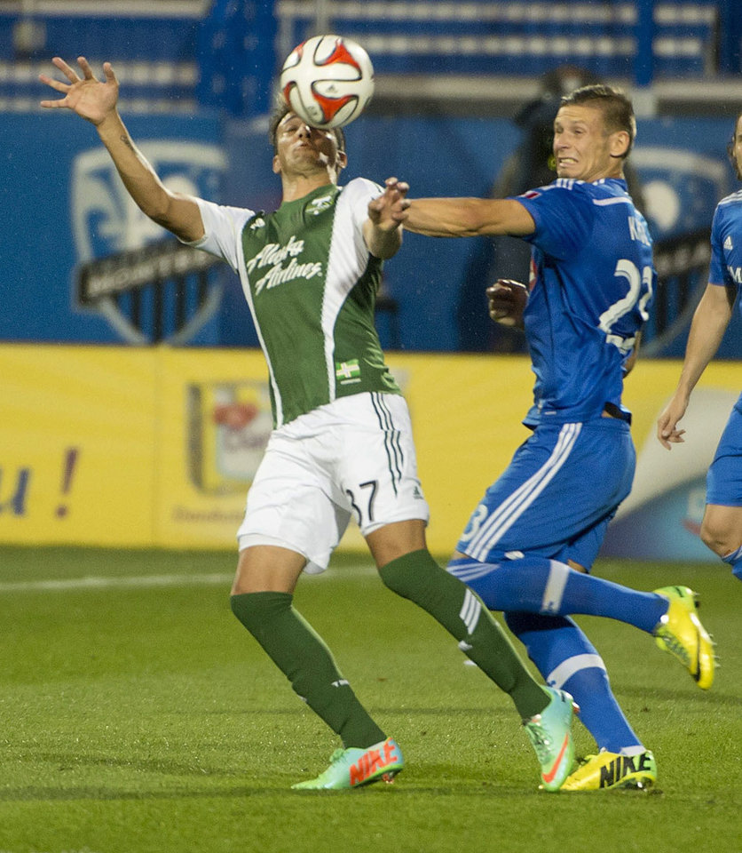 Photo - Portland Timbers' Maximiliano Urruti, left, and Montreal Impact's Krzysztof Krol vie for the ball during the first half of an MLS soccer game Sunday, July 27, 2014, in Montreal. (AP Photo/The Canadian Press, Peter McCabe)