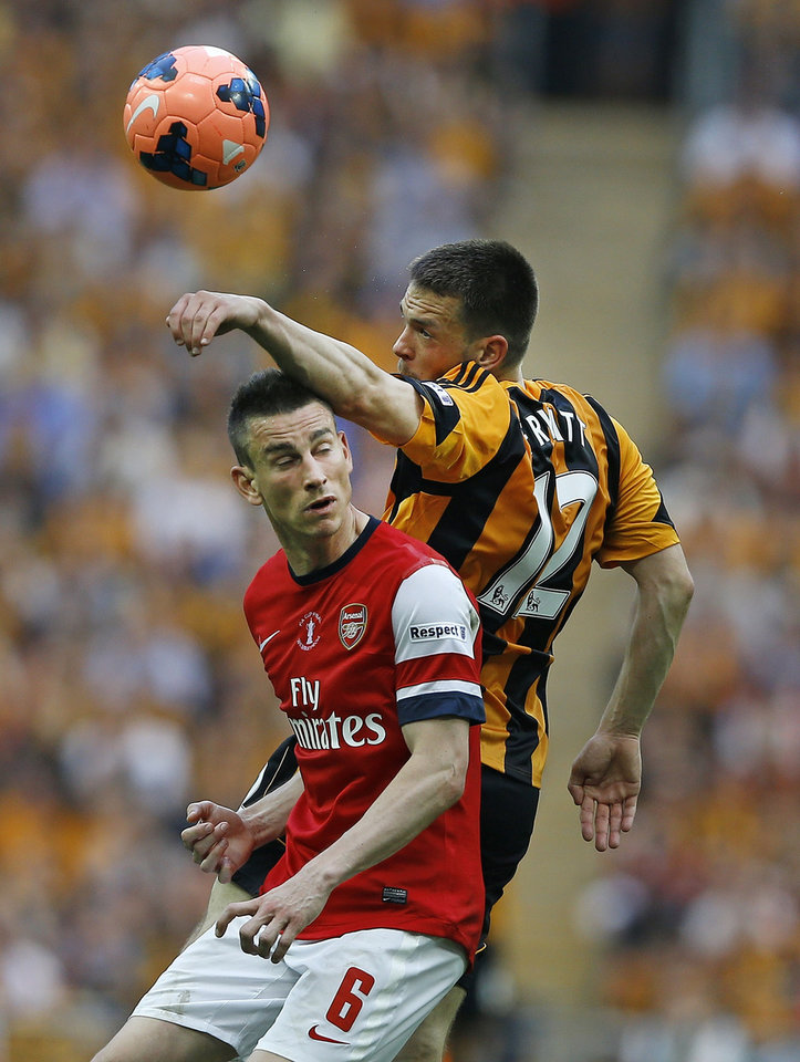 Photo - Arsenal's Laurent Koscielny, left, is challenged by Hull City's Matty Fryatt during the English FA Cup final soccer match between Arsenal and Hull City at Wembley Stadium in London, Saturday, May 17, 2014. (AP Photo/Kirsty Wigglesworth)