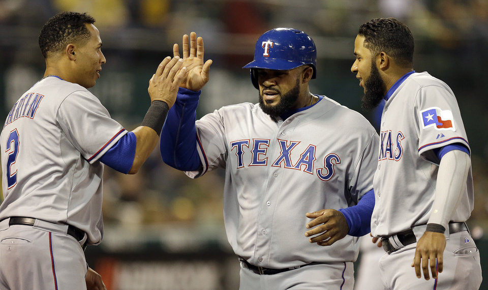 Photo - Texas Rangers' Prince Fielder, center, is congratulated by Leonys Martin, left, and Elvis Andrus after Fielder scored against the Oakland Athletics in the fourth inning of a baseball game Monday, April 21, 2014, in Oakland, Calif. Fielder scored on a single by Kevin Kouzmanoff. (AP Photo/Ben Margot)