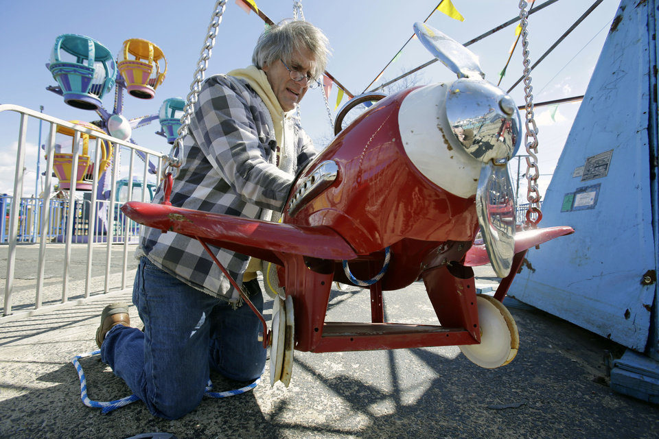 Hank Gehlhaus prepares the 1930's Kiddie Airplane Ride for opening day at The Keansburg Amusement Park, Saturday, March 23, 2013, in Keansburg, N.J. Founded in 1904, by Gehlhaus' grandfather, the Keansburg Amusement Park, which the Superstorm Sandy left under up to six feet of water, opens Saturday even though not all rides will be ready to operate and its popular Wildcat roller coaster is gone. (AP Photo/Mel Evans)