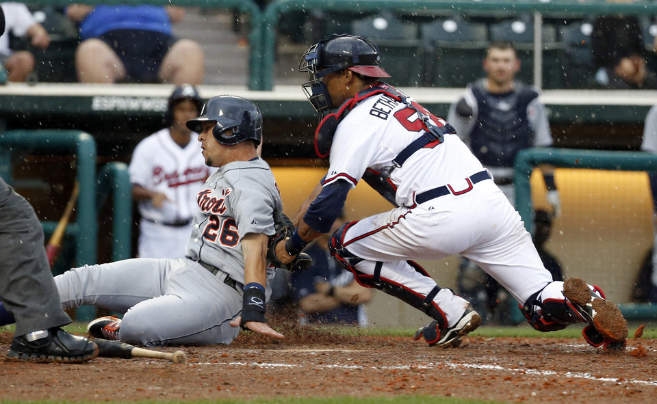 Photo - Atlanta Braves catcher Christian Bethancourt tags Detroit Tigers' Hernan Perez for the out at home in the ninth inning of a spring training baseball game, Wednesday, Feb. 26, 2014, in Kissimmee, Fla. The Tigers won 6-5. The game was stopped because of rain with two outs in the bottom of the ninth, and the Tigers were awarded the win. (AP Photo/Alex Brandon)