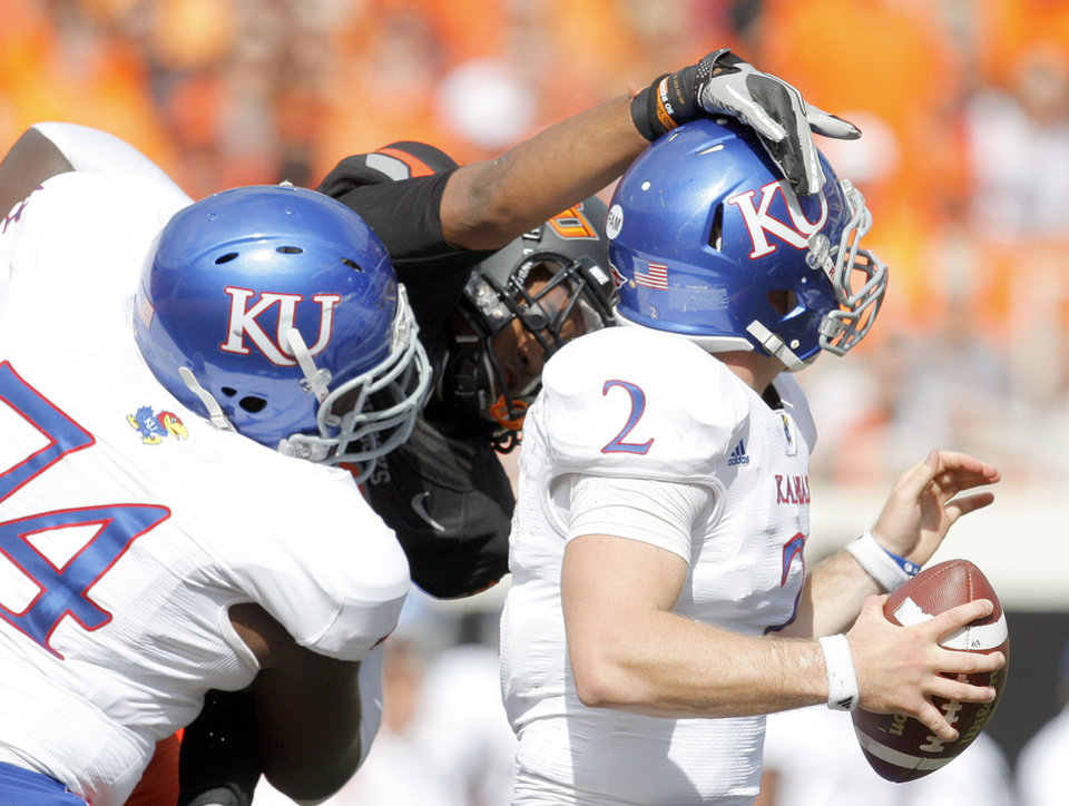 Oklahoma State's Cooper Bassett (80) pressures Kansas' Jordan Webb (2) as Kansas' Jeff Spikes (74) defends during the first half of the college football game between the Oklahoma State University Cowboys (OSU) and the University of Kansas Jayhawks (KU) at Boone Pickens Stadium in Stillwater, Okla., Saturday, Oct. 8, 2011. Photo by Sarah Phipps, The Oklahoman