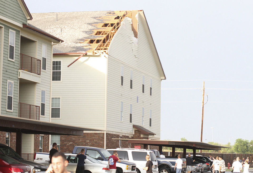 Residents mill around the parking lot at Independence Place Apartments on the east side of Lawton, Okla., after storm Monday, May 28, 2012 ripped a hole in the roof. High winds and large hail caused 8,500 customers to lose power, according to PSO.  (AP Photo/The Lawton Constitution,brandon  neris)         ORG XMIT: OKLAW103