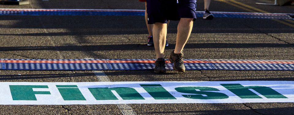 Photo - Runners make their way across the finish line during the Oklahoma City Marathon in Oklahoma City, Okla. on Sunday, April 29, 2018.  . Photo by Chris Landsberger, The Oklahoman