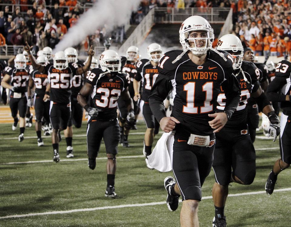 Photo - Zac Robsinson (11) and the OSU Cowboys take the field in black uniforms before the college football game between Oklahoma State University (OSU) and the University of Colorado (CU) at Boone Pickens Stadium in Stillwater, Okla., Thursday, Nov. 19, 2009. Photo by Nate Billings, The Oklahoman