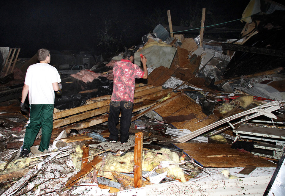 Photo -   Two men look for people who may be trapped underneath rubble at Pinaire Mobile Home Park after it was struck by a reported tornado, in Wichita, Kan., Saturday night, April 14, 2012. (AP Photo/The Wichita Eagle, Chris Neal)