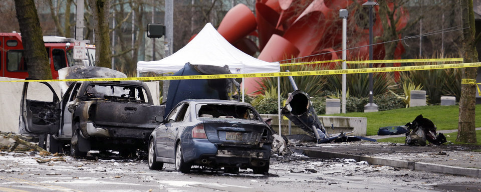 Photo - Caution tape surrounds the charred wreckage of a news helicopter and two vehicles after the chopper crashed into a city street near the Space Needle, Tuesday, March 18, 2014, in Seattle. Two people were killed and another was critically injured, according to the Seattle Fire Department. (AP Photo/Elaine Thompson)