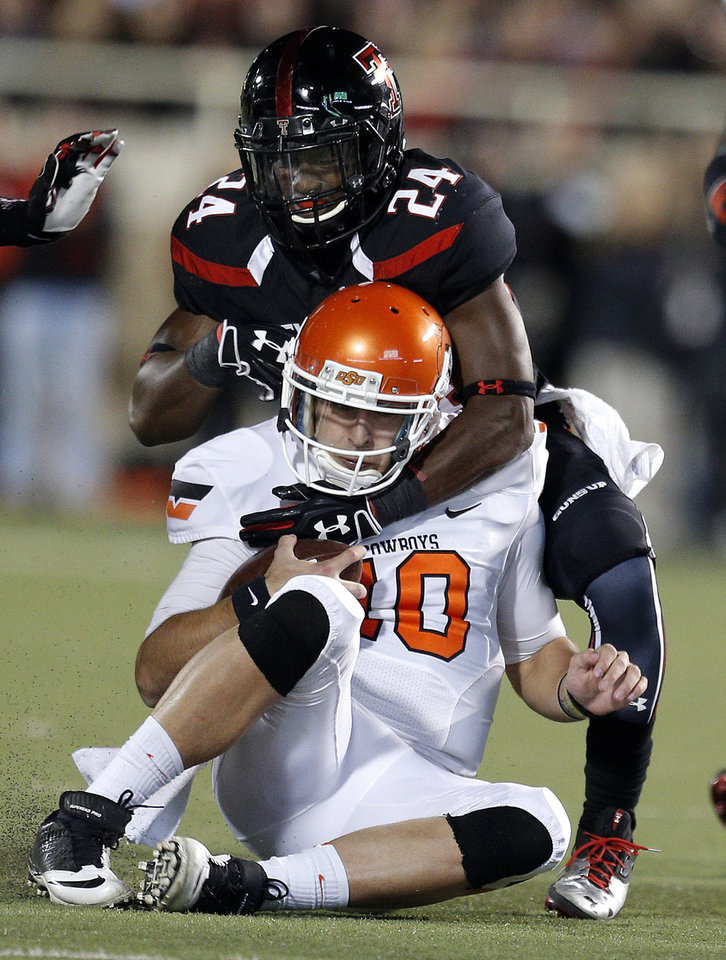 Oklahoma State 's Clint Chelf (10) is tackled by Texas Tech's Bruce Jones (24) during the college football game between the Oklahoma State Cowboys (OSU) and the Texas Tech Red Raiders (TTU) at Jones AT&T Stadium in Lubbock, Texas, Saturday, Nov. 2, 2013. Photo by Sarah Phipps, The Oklahoman
