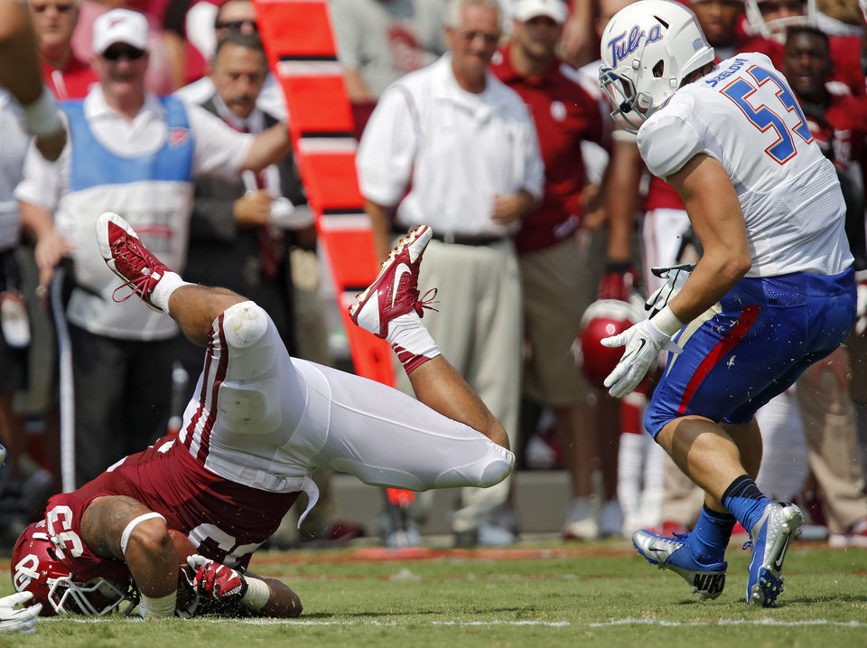 Oklahoma's Trey Millard (33) is upended on a play in front of Tulsa 's Jake Sizelove (53) during the college football game between the University of Oklahoma Sooners (OU) and the University of Tulsa Hurricanes (TU) at the Gaylord-Family Oklahoma Memorial Stadium on Saturday, Sept. 14, 2013 in Norman, Okla.  Photo by Chris Landsberger, The Oklahoman