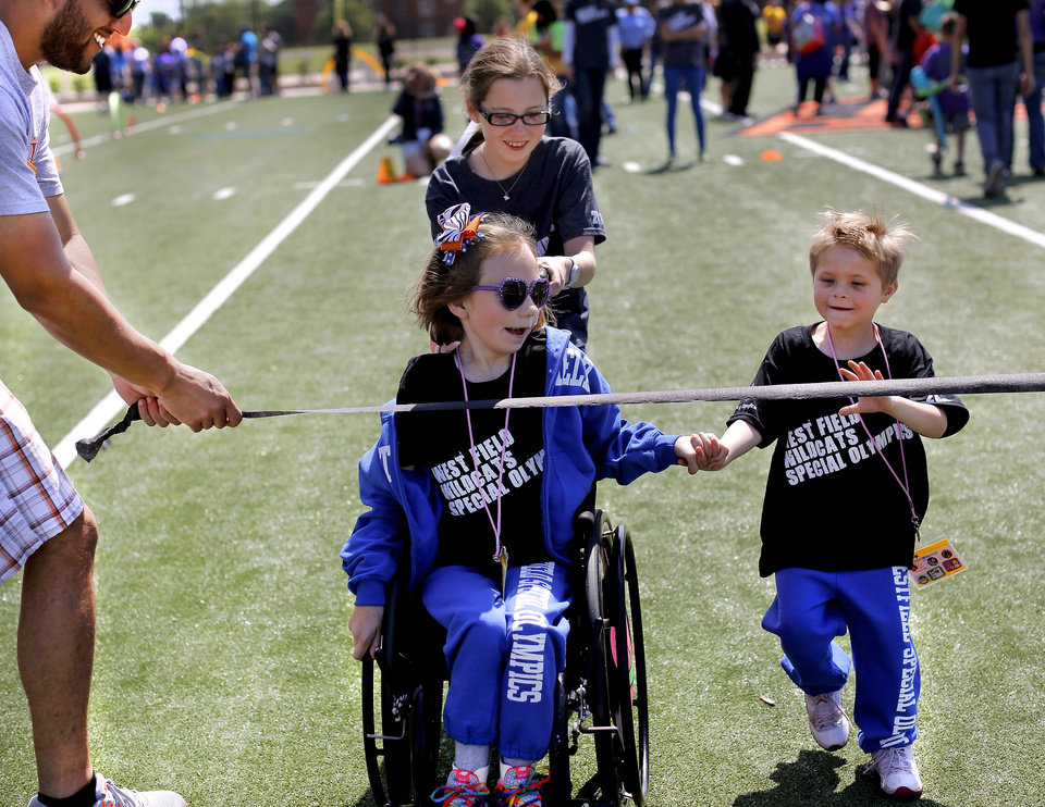Photo - Addison Mesa, 7, in wheel chair, holds the hand of her good friend Christian Millspaugh, 6, as they near the finish line in a short race in the 'Stars of the Future' area north of Boone Pickens Stadium on the campus of Oklahoma State University on Thursday, May 15, 2014. Pushing Addison's chair is her sister, Megan Mesa, 9. The children attend West Field Elementary School in Edmond. Special Olympics athletes numbering in the thousands are competing in various events today and tomorrow  in Stillwater as the organization's 45th Annual Summer Games are held in Oklahoma this week.  Officials say more than 4,600 Special Olympics Oklahoma athletes have registered to compete this year, and thousands of volunteers are assisting during the three days of competitions.   This is the 31st year the summer games has been centered at Oklahoma State University.  Special Olympics is the world's largest sports organization for children and adults with intellectual disabilities, providing year-round training and competitions to more than 4.2 million athletes in 170 countries, according to their web site. Photo by Jim Beckel, The Oklahoman