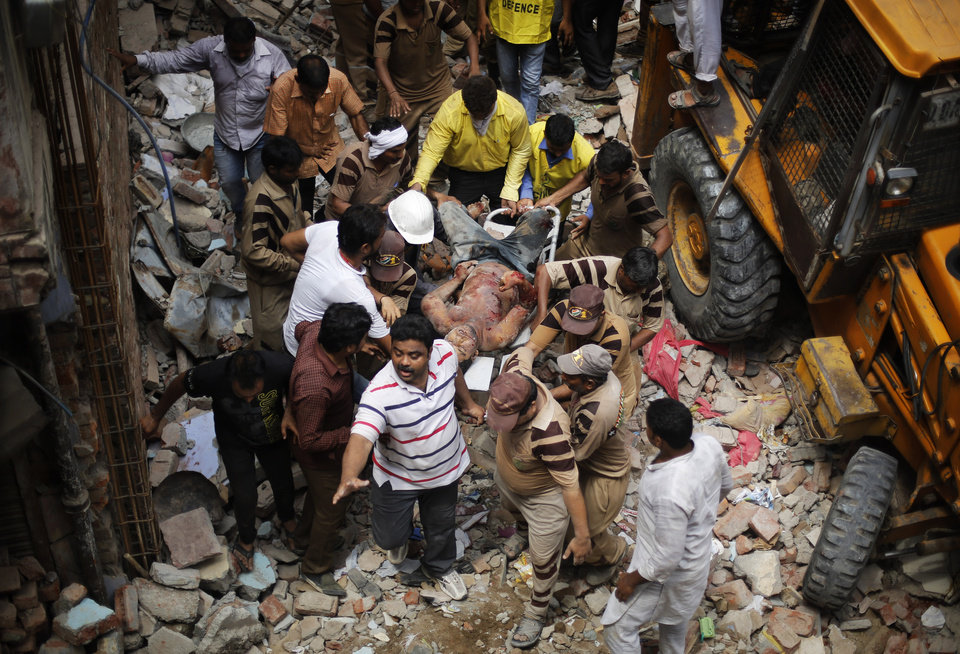 Photo - EDS NOTE: GRAPHIC CONTENT - Rescue workers carry the body of a victim out of the debris of a building that collapsed in New Delhi, India, Saturday, June 28, 2014. A dilapidated building collapsed in the Indian capital on Saturday, killing at least seven people as rescuers searched for others believed to be trapped. (AP Photo/Altaf Qadri)