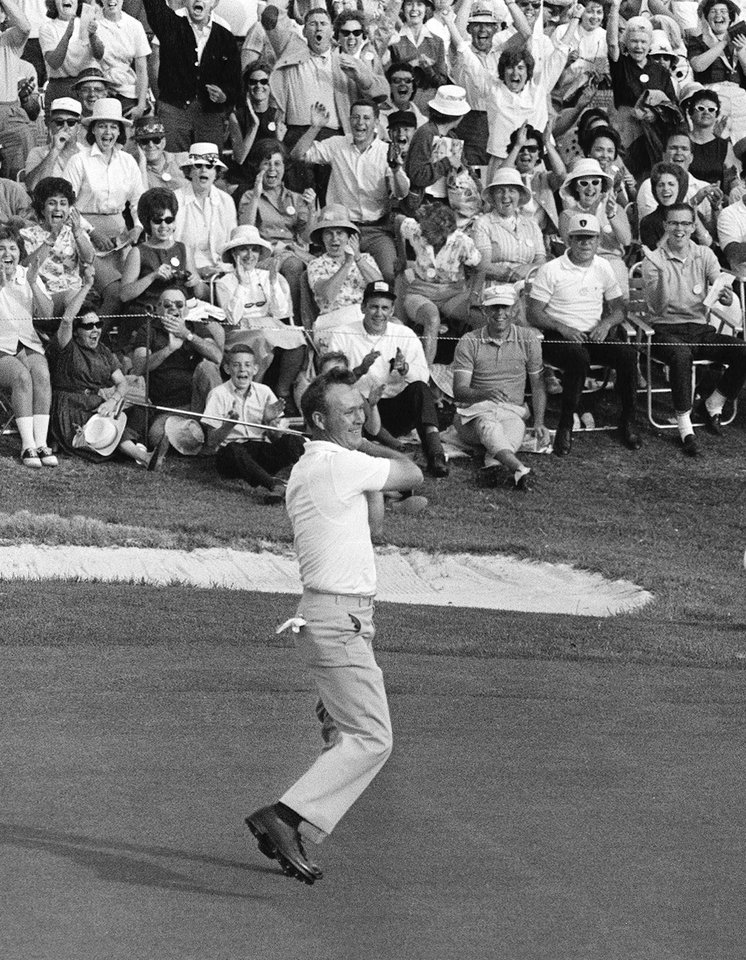 Photo - FILE - In this April 12, 1964 file photo, Arnold Palmer swings his putter after he rolled in a long birdie putt on 18 to win his fourth Masters golf tournament, in Augusta, Ga.  Fifty years ago, Palmer won the Masters for the fourth time. It was his seventh major. He was 34, the King.  (AP Photo/File)