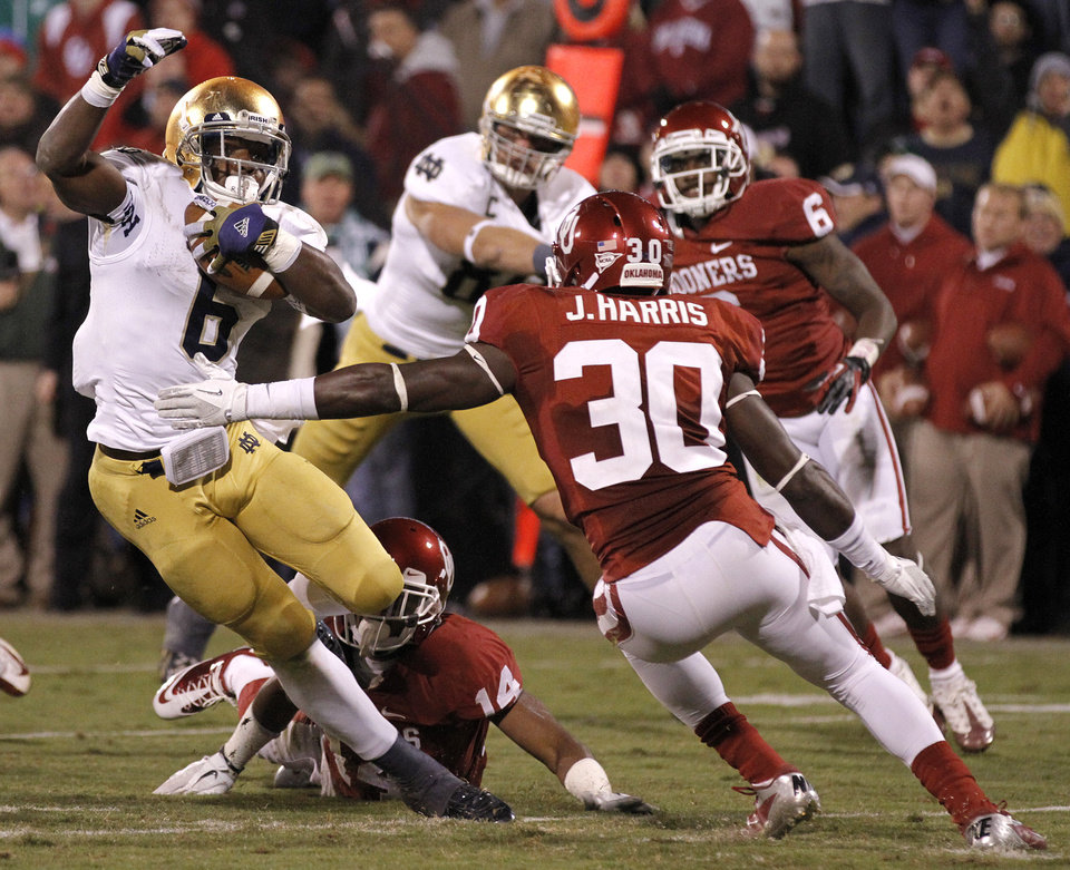 Notre Dame 's Theo Riddick (6) cuts by OU's Javon Harris (30) for a touchdown during the college football game between the University of Oklahoma Sooners (OU) and the Notre Dame Fighting Irish at the Gaylord Family-Oklahoma Memorial Stadium on Saturday, Oct. 27, 2012, in Norman, Okla. Photo by Chris Landsberger, The Oklahoman