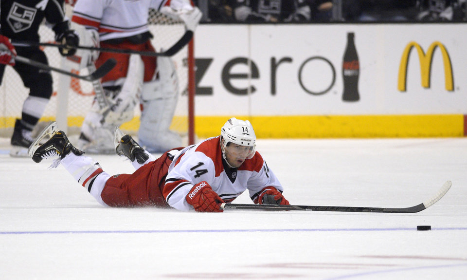 Photo - Carolina Hurricanes left wing Nathan Gerbe dives for the puck during the first period of an NHL hockey game against the Los Angeles Kings, Saturday, March 1, 2014, in Los Angeles. (AP Photo/Mark J. Terrill)