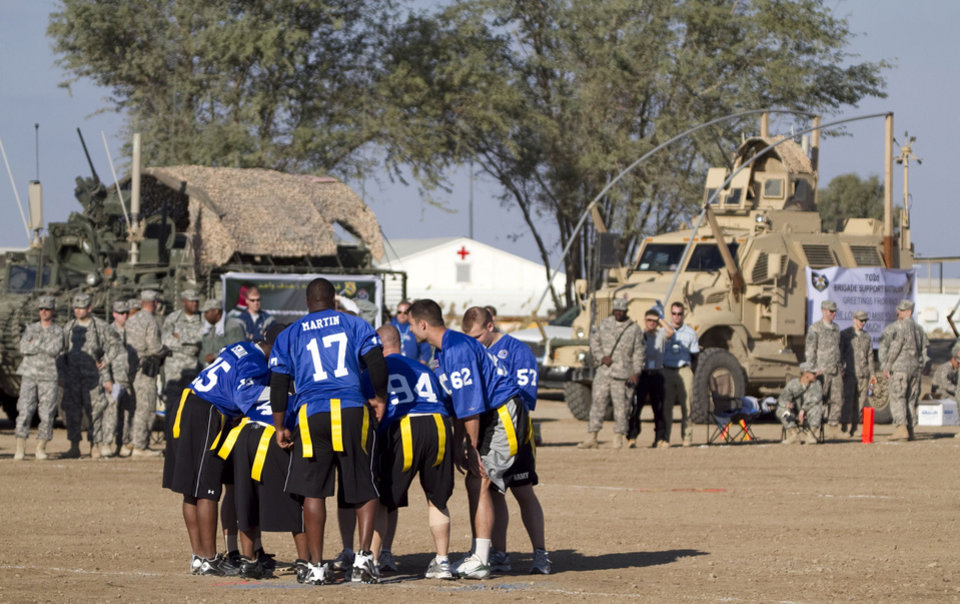 """Team Liberty huddles as troops watch in front of MRAP's during the first-ever Tostitos/USO """"Salute the Troops"""" Bowl, where legendary college football players played alongside troops in Baghdad, Iraq, January 1, 2010.  Team Freedom, led by coach Barry Switzer, beat Team Liberty which was led by coach Tommy Bowden.     ORG XMIT: 1001042350042901"""