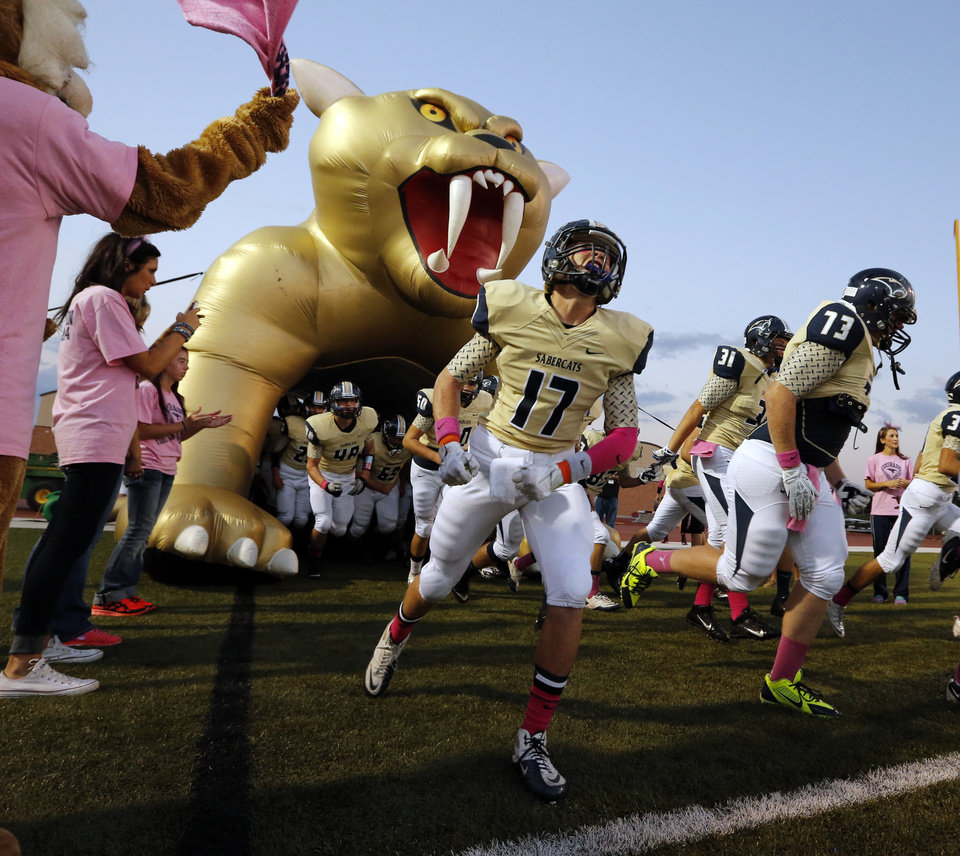 Photo - Sabercats take the field as the Southmoore  plays Lawton in high school football on Friday, Oct. 11, 2013, in Moore, Okla. Photo by Steve Sisney, The Oklahoman