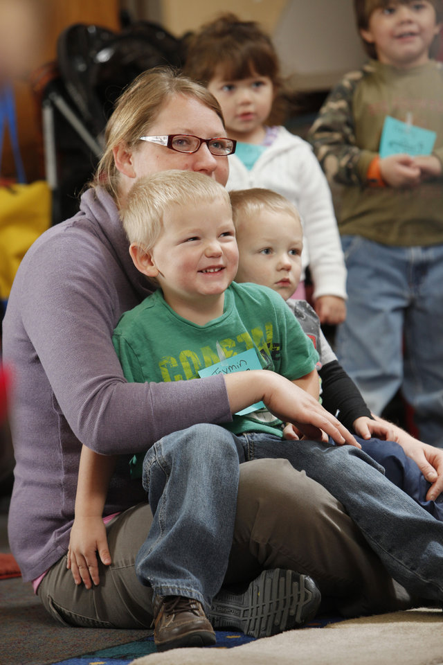 Melissa Sattler and sons Jaymin, 3, and Gabriel, 2, listen as Sarah Fox, children\'s services assistant for the Norman Public Lobrary, leads family story time on Saturday, Jan. 21, 2012, in Norman, Okla. Photo by Steve Sisney, The Oklahoman