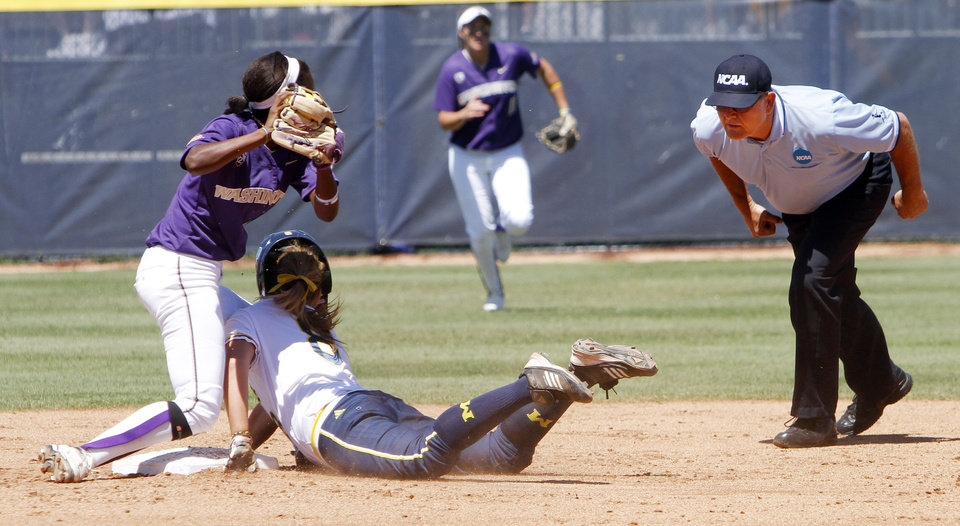 Photo - Washington Huskies short stop Jenni McNeill tags Michigan baserunner Ashley Lane out as she slides into second during the Women's College World Series elimination game versus Michigan. The Washington Huskies would won 4-1 on June 2, 2013. Photo by KT KING, The Oklahoman