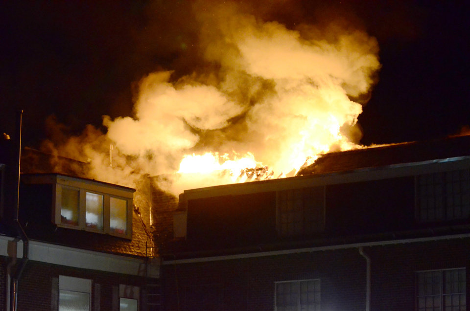 In this photo taken on Tuesday, Jan. 14, 2014, flames shoot through a roof where Norman (Okla.) firefighters battle a late-night blaze at the Alpha Gamma Delta sorority house on the campus of the University of Oklahoma in Norman. Okla. No one was injured  and investigators don't yet know what caused the fire but say it likely started in the building's attic. Members of the sorority are staying in temporary housing until they can safely return to the house. (AP Photo/The Norman Transcript, Kyle Phillips)