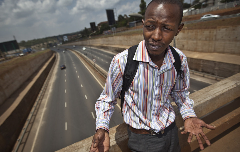 ADVANCE FOR MONDAY, DEC. 3. - In this Oct. 10, 2012 photo, Anthony Mwaura, a 23-year-old marketing student, stands on a bridge a new 50-kilometer (30-mile) highway leading north of the capital of Nairobi in Kenya. The $300 million road was built by three Chinese companies and financed by the African Development Bank and the Chinese Exim Bank. It has cut a trip that took several hours 18 months ago to 10 minutes, said Joseph Makori, a professional driver. (AP Photo/Ben Curtis)