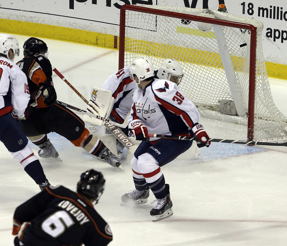 Photo - Anaheim Ducks defenseman Ben Lovejoy (6) puts the puck in the net against Washington Capitals goalie Jaroslav Halak (41), of Slovakia, and defenseman Jack Hillen (38) in the first period of an NHL hockey game Tuesday, March 18, 2014. (AP Photo/Reed Saxon)