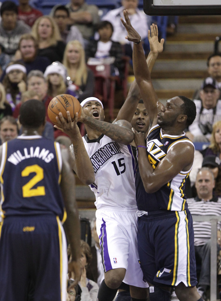 Photo -   Sacramento Kings center DeMarcus Cousins, center, is fouled by Utah Jazz center Al Jefferson, right, during the first half of an NBA basketball game in Sacramento, Calif., Saturday, Nov. 24, 2012. (AP Photo/Rich Pedroncelli)