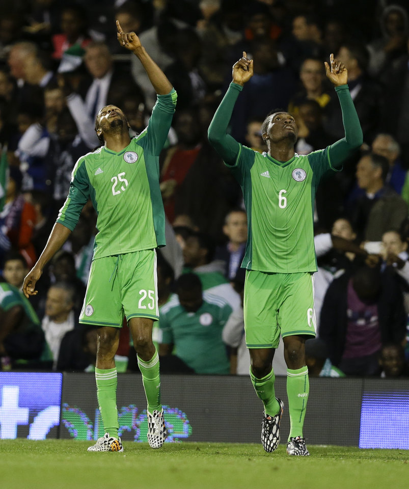 Photo - Nigeria's Michael Uchebo, left, celebrates with Azubuike Egwueke after he scores a goal during the international friendly soccer match between Nigeria and Scotland at Craven Cottage Stadium in London, Wednesday, May 28, 2014. Nigeria will be in Group F in the upcoming World Cup in Brazil. (AP Photo/Kirsty Wigglesworth)