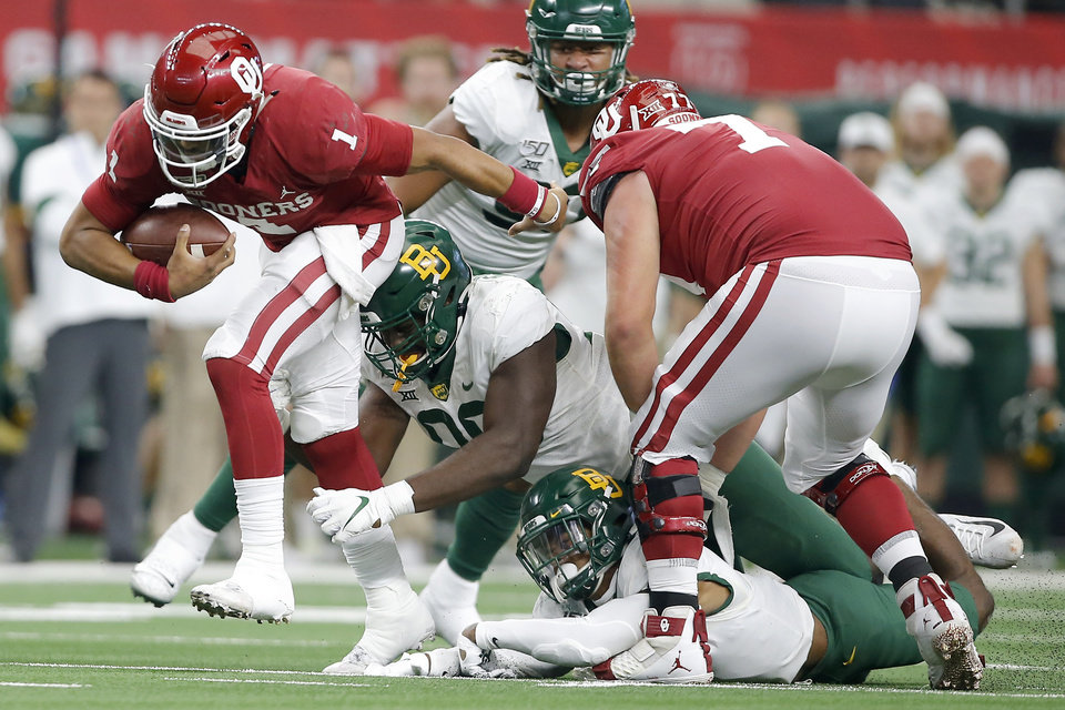 Photo - Oklahoma's Jalen Hurts (1) tries to get away from Baylor's Chris Miller, bottom right, and Chidi Ogbonnaya during the Big 12 Championship Game between the University of Oklahoma Sooners (OU) and the Baylor University Bears at AT&T Stadium in Arlington, Texas, Saturday, Dec. 7, 2019. Oklahoma won 30-23. [Bryan Terry/The Oklahoman]