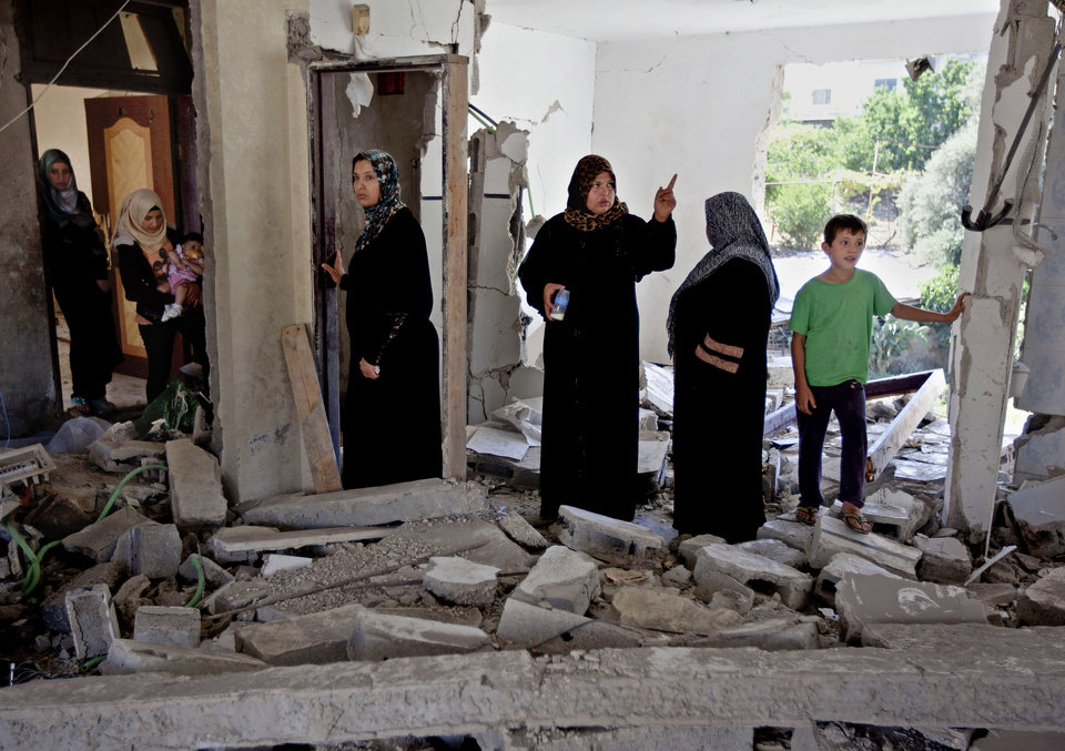 Photo - Palestinian women and children inspect the damaged family home of Ziad Awad in the town of Idna, 13 kilometers (8 miles) west of the West Bank city of Hebron, Wednesday, July 2, 2014. Israel demolished on Wednesday the home of Ziad Awad, who it accuses of having killed an Israeli police officer in April. The move marks a return to a policy abandoned by the military in 2005. Israel sees house demolitions as a deterrent to violence while critics charge it is a form of collective punishment. (AP Photo/Majdi Mohammed)