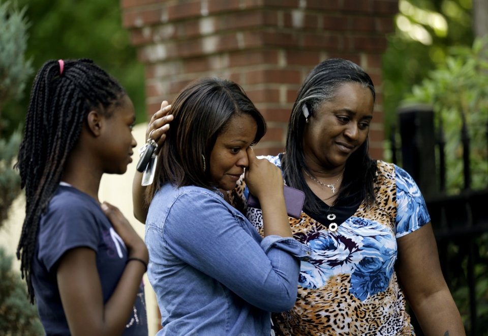 Photo - Dezmonee Selbey, center, is comforted by her mother Darretta Rhone, right, and sister Imani Rhone as they look over a memorial of flowers outside the home of Maya Angelou in Winston-Salem, N.C., Wednesday, May 28, 2014. Angelou has died at the age of 86. (AP Photo/Gerry Broome)
