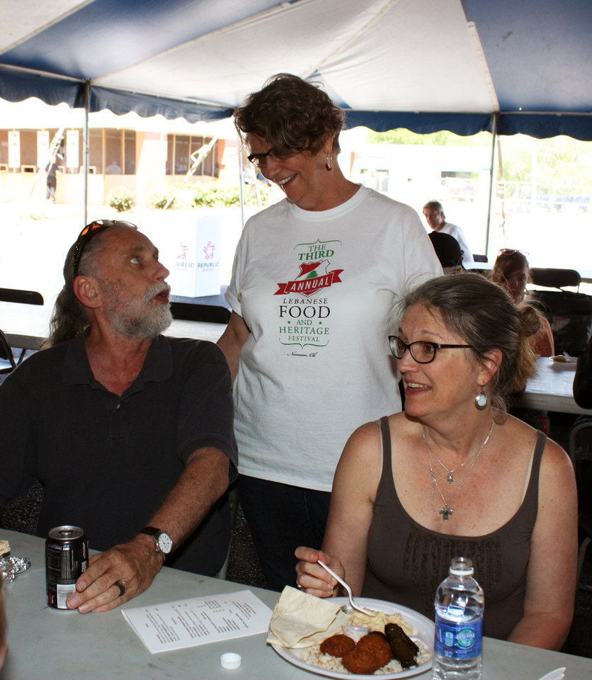 Photo -  Patty Jazzar, center, chats with Dave and Pam Boeck at the third annual Lebanese Heritage and Food Festival at Our Lady of Lebanon Church in Norman. PHOTO BY LYNETTE LOBBAN, FOR THE OKLAHOMAN