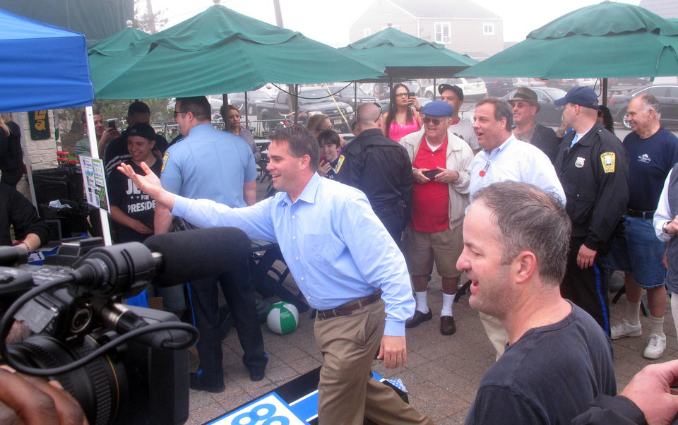 Photo - Belmar N.J. Mayor Matt Doherty, left, plays a game of bean bag toss with New Jersey Gov. Chris Christie on the foggy  Belmar beachfront on Friday May 23, 2014. Christie said the Jersey Shore has made great strides recovering from Superstorm Sandy in Oct. 2012. (AP Photo/Wayne Parry)