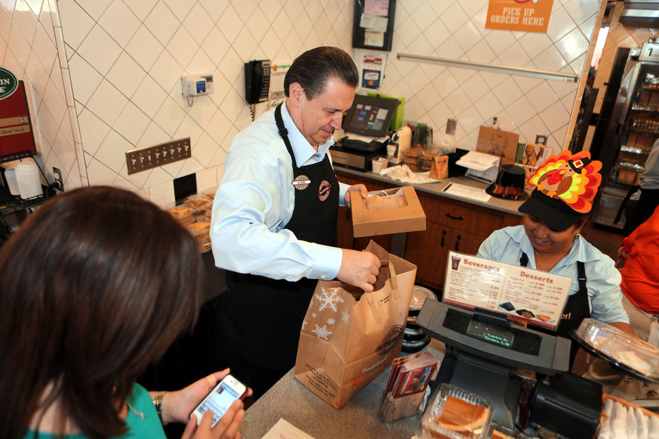 Photo - This Nov. 22, 2012 photo provided by Boston Market shows Boston Market CEO George Michel, center, working inside a company's Miami-area restaurant on the home style restaurant chains busiest day of the year, Thanksgiving, in Miami. Boston Market Corp. is reporting record Thanksgiving sales this year, and it's already planning for next Thanksgiving.The Golden, Colo.-based restaurant chain had not yet released specific dollar figures but said total sales per restaurant from Nov. 19 to Nov. 23 were up 13 percent from a comparable period last year. (AP Photo/Boston Market, Marc Serota)