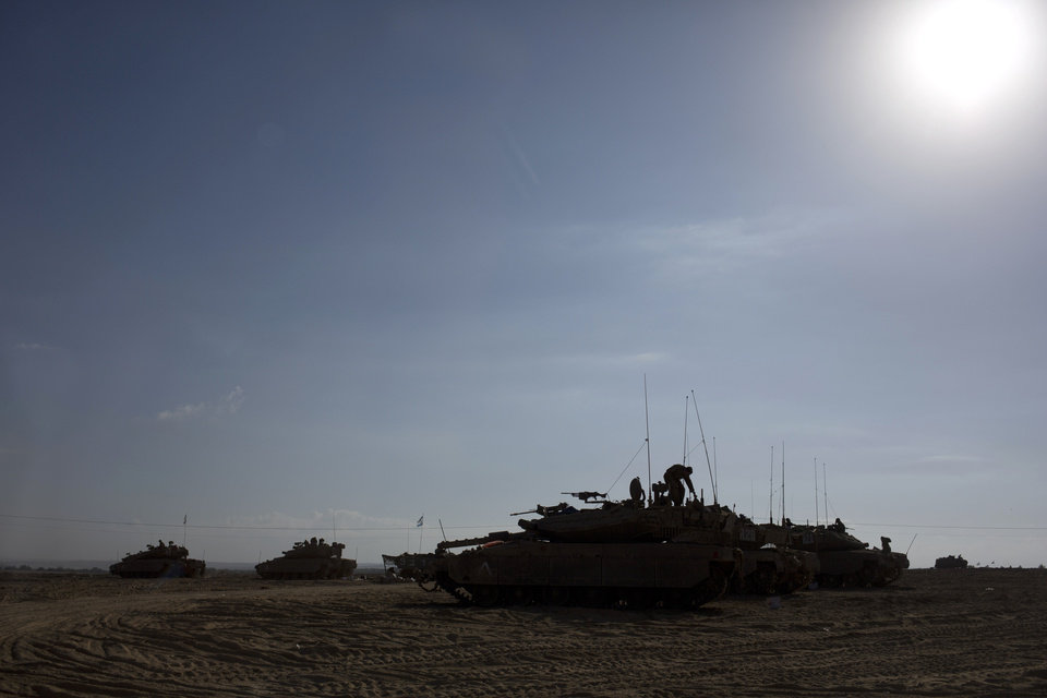 Photo - Israeli soldiers work on their tanks near the Israel and Gaza border Friday, July 25, 2014. Early Friday, Israeli warplanes struck tens of houses throughout the Gaza Strip as international efforts continue to broker a cease fire in the 18 day-old war. (AP Photo/Dusan Vranic)