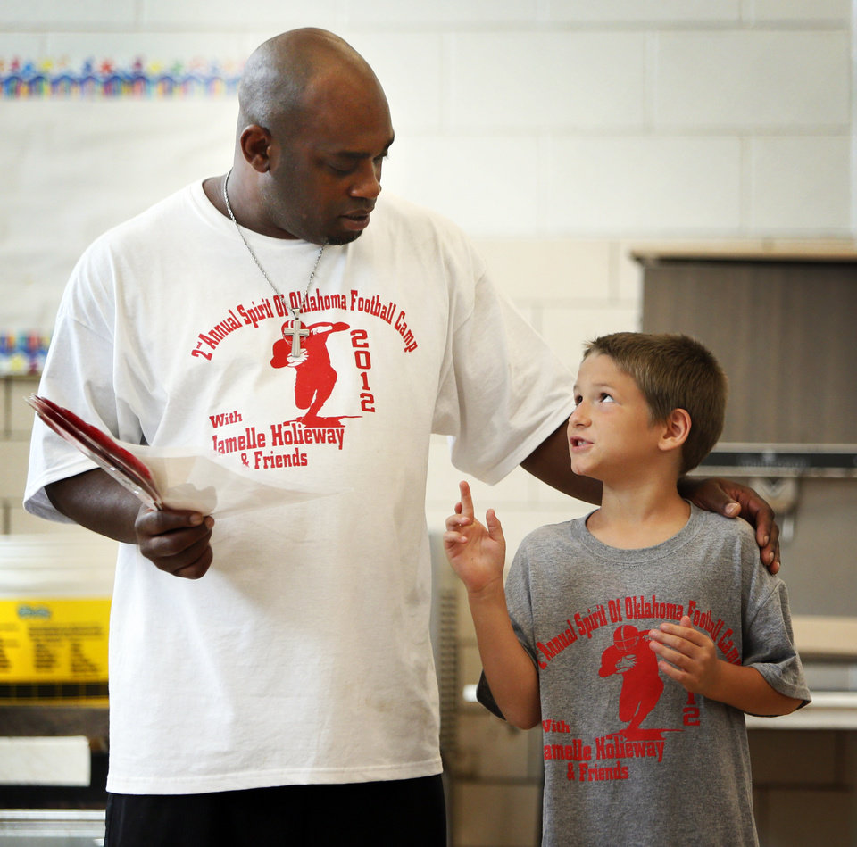 Photo - Former OU quarterback Jamelle Holieway talks with Sebastian Thompson, 8, as he gives Thompson an autographed picture of Brian Bosworth as an award for his hard work during Holieway's Spirit of Oklahoma football camp in Weleetka, Okla., Friday, July 6, 2012. Photo by Nate Billings, The Oklahoman