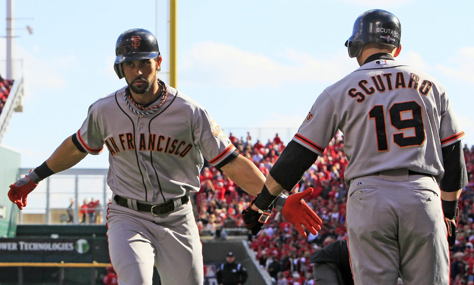 San Francisco Giants' Angel Pagan is congratulated by Marco Scutaro (19) after Pagan hit a solo home run in the first inning of Game 4 of the National League division baseball series against the Cincinnati Reds, Wednesday, Oct. 10, 2012, in Cincinnati. (AP Photo/Al Behrman)